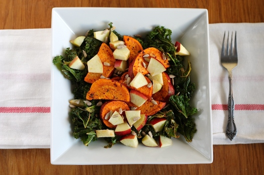 Warm roasted salad with kale, sweet potatoes, apple, and sunflower seeds.