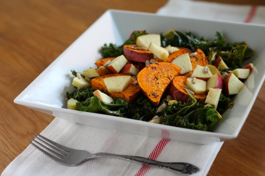 Warm roasted salad with kale, sweet potatoes, apple, and sunflower seeds