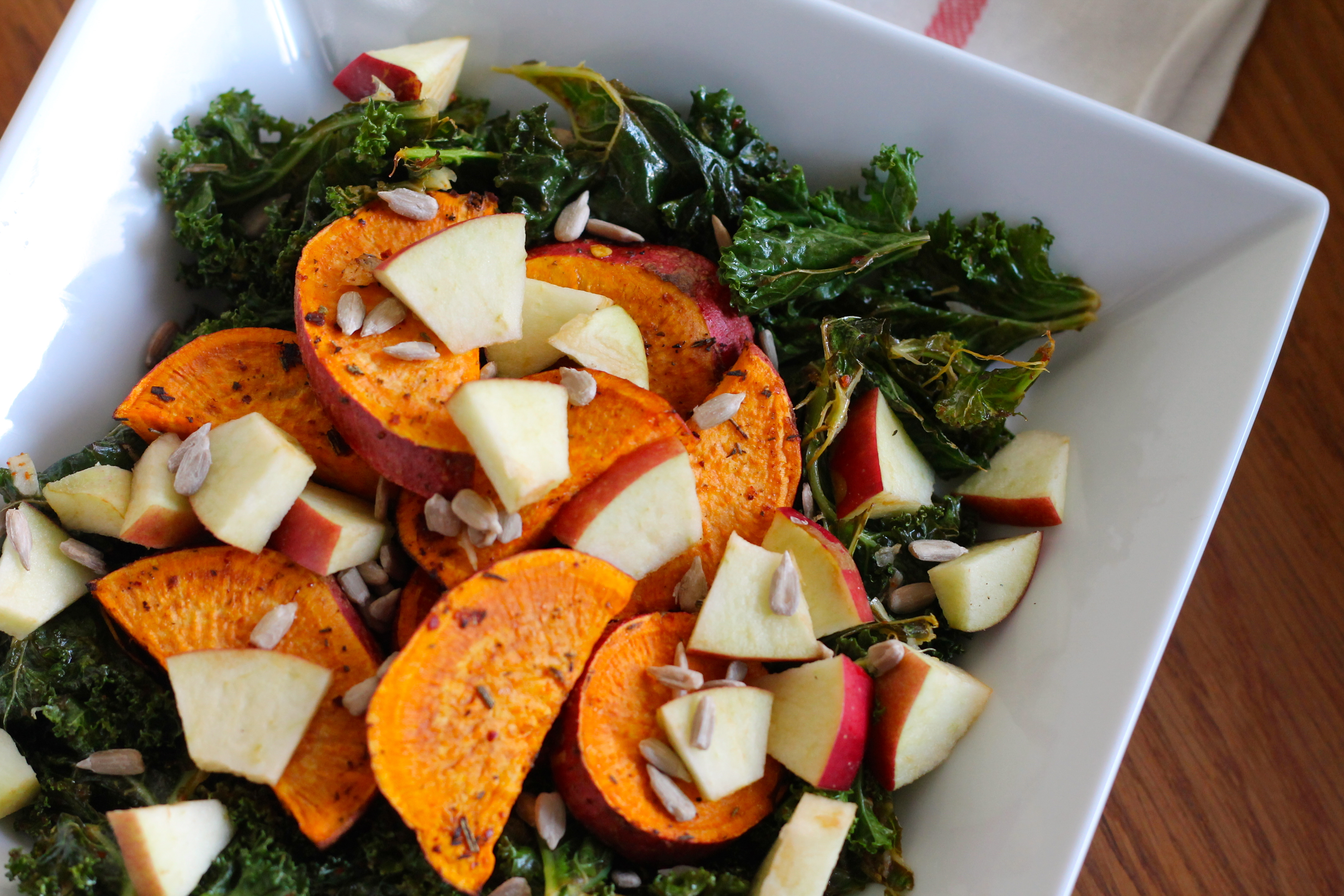 Warm salad with roasted kale, sweet potatoes, apples, and sunflower seeds